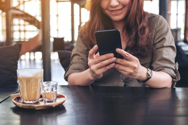 Close-upbeeld van een vrouw die slimme telefoon met koffiekop op houten lijst houdt, gebruikt en bekijkt