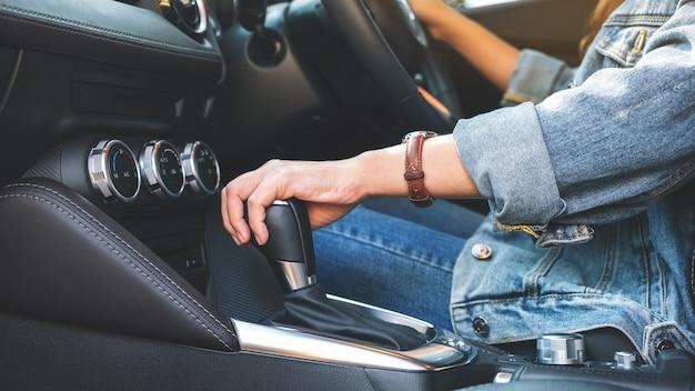 Close-upbeeld van een vrouwelijke bestuurder die automatische versnellingspook verschuift tijdens het autorijden