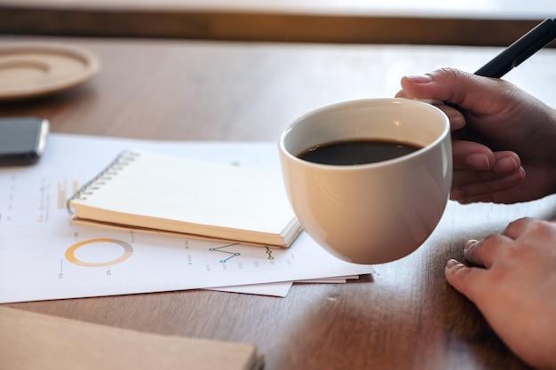 Close-upbeeld van een vrouwenhand die een kop hete koffie houdt terwijl u aan bedrijfsdocument op houten lijst werkt