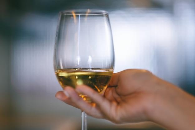 Close-upbeeld van een vrouwenhand die een wijnglas met onscherpe achtergrond houdt Premium Foto