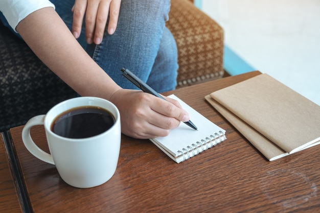 Close-upbeeld van een vrouwenhand die op leeg notitieboekje met koffiekop op houten lijst schrijft