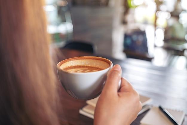 Close-upbeeld van een vrouwenholding en het drinken van hete koffie