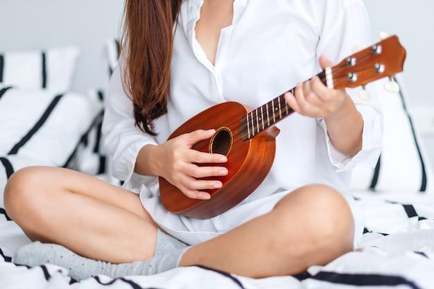 Close-upbeeld van een vrouwenzitting en het spelen ukelele in slaapkamer