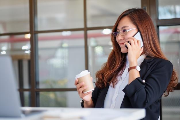 Close-upbeeld van een zakenvrouw die een kopje koffie vasthoudt terwijl ze op een mobiele telefoon op kantoor praat