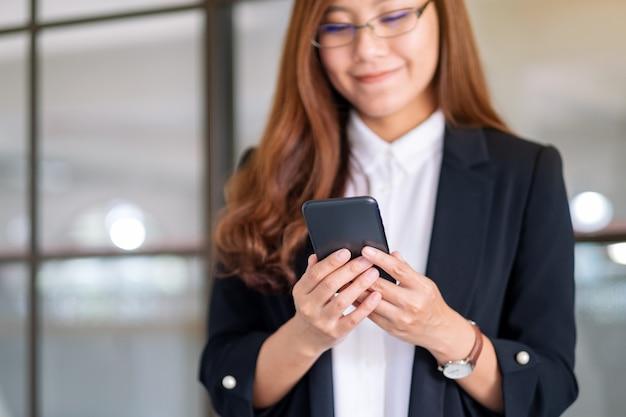 Close-upbeeld van een zakenvrouw die een mobiele telefoon vasthoudt en gebruikt