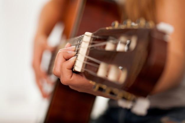 Close-upbeeld van gitaar in vrouwenhanden