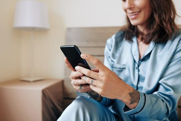 Close-upbeeld van glimlachende jonge vrouw die vrienden sms't na het opstaan in de ochtend