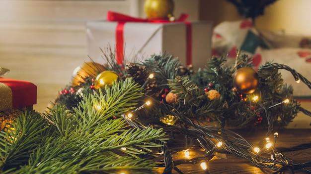 Close-upbeeld van gloeiende kerstverlichting en geschenkdozen met linten onder de kerstboom