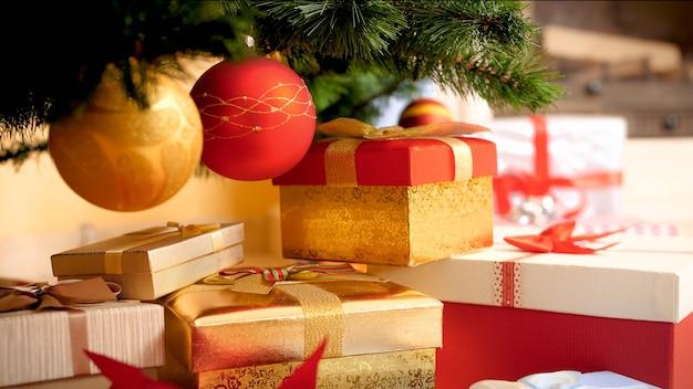 Close-upbeeld van gouden en rode kerstballen die aan de kerstboom hangen boven een grote hoop geschenken en cadeautjes in dozen in de woonkamer