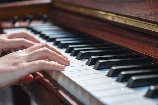 Close-upbeeld van handen die een uitstekende houten vleugel spelen