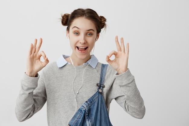 Close-upbeeld van het aantrekkelijke vrouw tonen in orde met vingers die van muziek van hoofdtelefoons genieten. volwassen vrouwtje in een goed humeur na het luisteren audioboek met haar smartphone. lichaamstaal