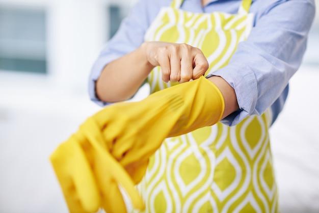 Close-upbeeld van huisvrouw die rubberhandschoenen aantrekken alvorens af te wassen of het huis schoon te maken