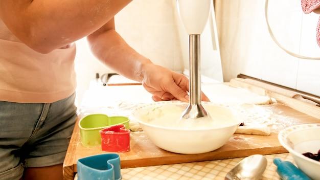 Close-upbeeld van jonge vrouw die ingrediënten in kom mengt tijdens het koken