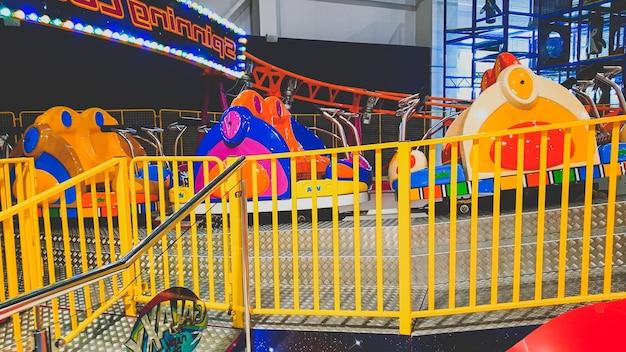 Close-upbeeld van kleurrijke elektrische auto's op de carrousel in pretpark bij winkelcentrum