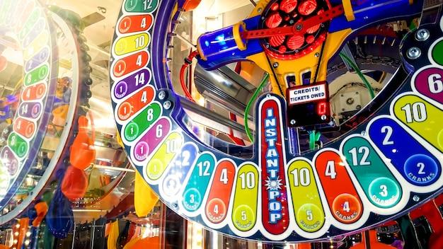Close-upbeeld van kleurrijke verlichte neonvertoning op de éénhandige trekgokmachine in casino. trek aan de hendel en grijp uw kans om een prijs of jackpot te winnen in de loterij