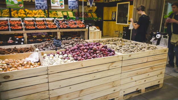 Close-upbeeld van knoflook, uien, aardappels en andere verse groenten die in houten kratten in kruidenierswinkelopslag liggen