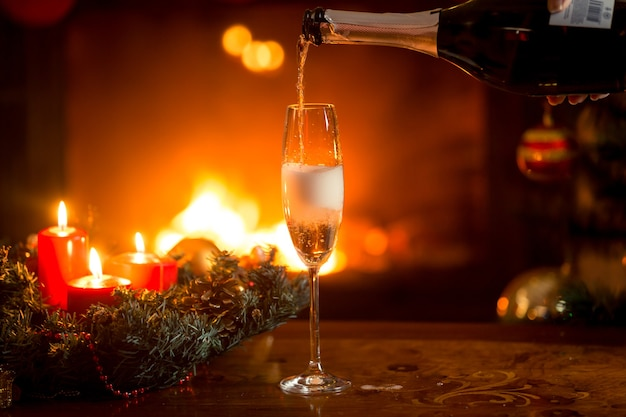 Close-upbeeld van kristalglas dat met champagne wordt gevuld. brandende open haard en kerstboom op de achtergrond