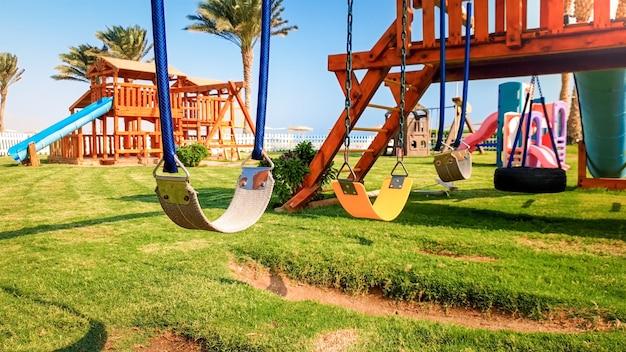 Close-upbeeld van lege schommels op de kinderspeelplaats bij heldere zonnige dag. niemand speelt in het park