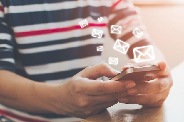 Close-upbeeld van mannelijke handen die smartphone met e-mail van de pictogramenvelop gebruiken