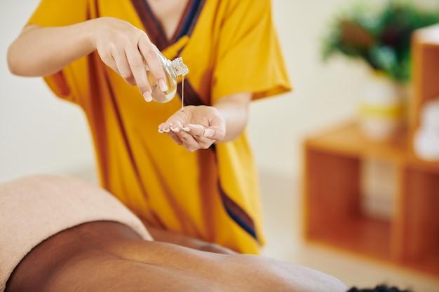 Close-upbeeld van masseur die organische olie in hand gieten om het op te warmen alvorens terug van jonge vrouw te masseren