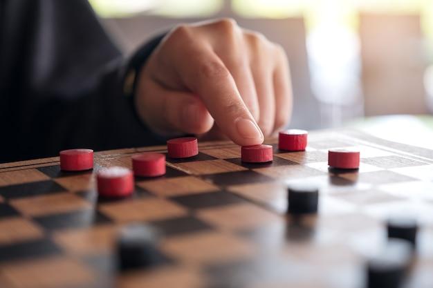 Close-upbeeld van mensen die en controleurs in een schaakbord spelen bewegen