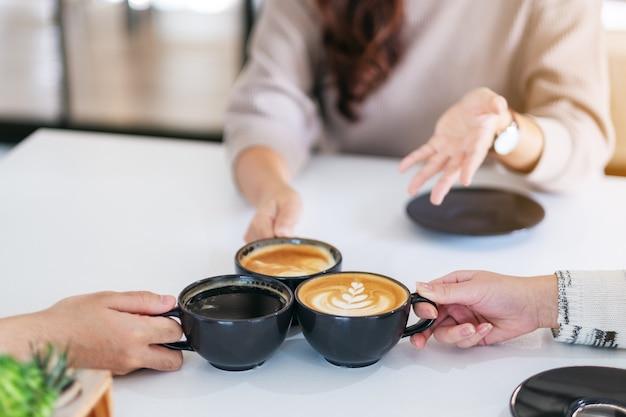Close-upbeeld van mensen die genoten van het drinken en rammelen van koffiekopjes op tafel in café