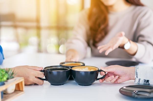 Close-upbeeld van mensen die graag praten terwijl ze drinken en koffiekopjes op tafel in café rammelen