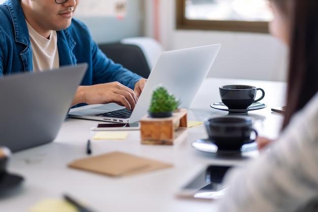 Close-upbeeld van mensen die laptopcomputer en tablet-pc gebruiken en erop werken op de tafel in kantoor