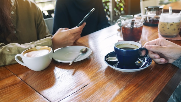 Close-upbeeld van mensen die mobiele telefoon gebruiken en samen koffie drinken in café