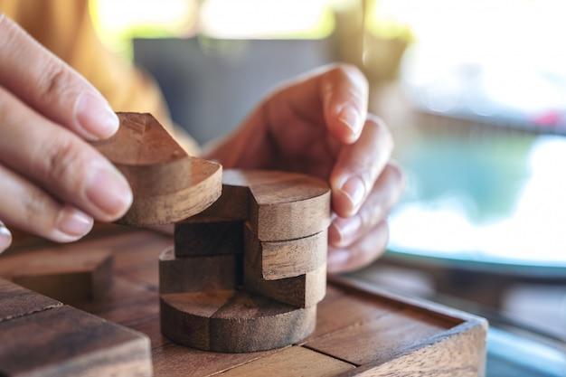 Close-upbeeld van mensen die rond houten puzzelspel spelen en bouwen