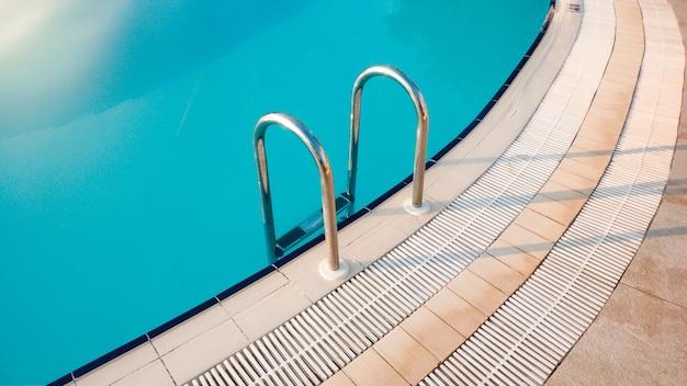 Close-upbeeld van metalen starcase aan het zwembad op vroege zonnige ochtend