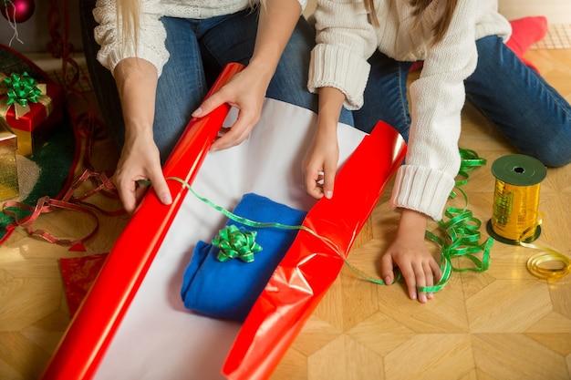 Close-upbeeld van moeder en dochter die een kerstcadeau maken en een trui in rood inpakpapier wikkelen