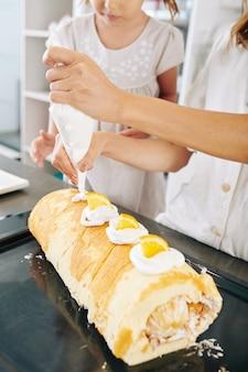 Close-upbeeld van moeder en dochter die zwitsers broodje met slagroom en plakjes mandarijn verfraaien