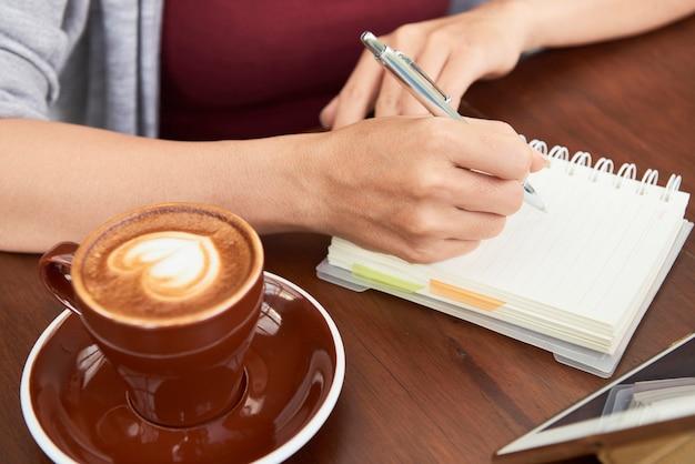 Close-upbeeld van onderneemster die ochtendkoffie in coffeeshop drinkt en gedachten en ideeën in planner schrijft