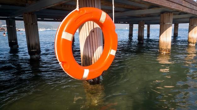 Close-upbeeld van oranje levensreddende ring die op houten pijler op zeestrand hangt