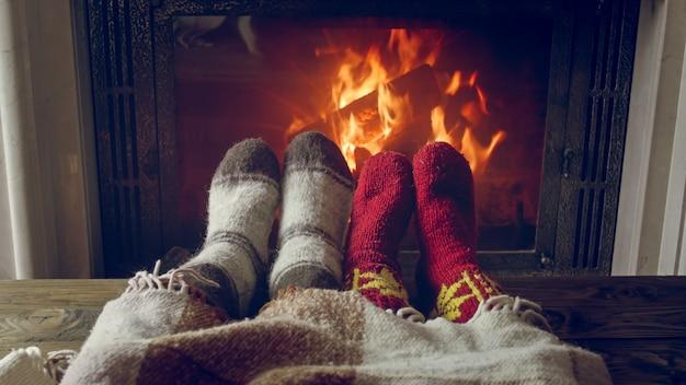 Close-upbeeld van paar in gebreide sokken die bij de open haard bij huis opwarmen