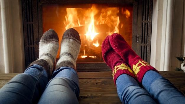 Close-upbeeld van paar in jeans en wollen sokken die bij de open haard liggen