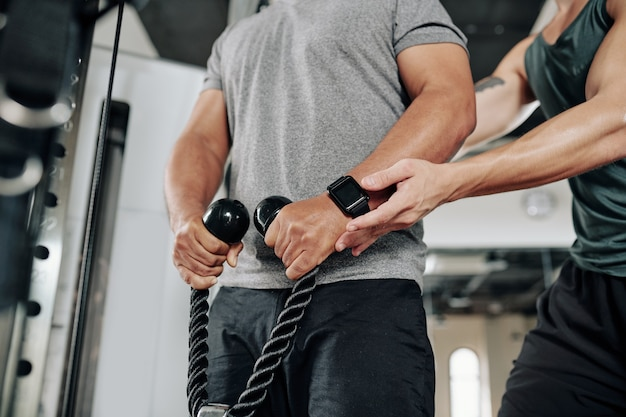 Close-upbeeld van persoonlijke fitnesstrainer die cliënt uitlegt hoe hij de kabel moet vasthouden om de oefening in de crossover-machine op te heffen