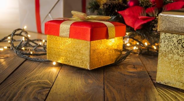 Close-upbeeld van rode kerstcadeaudoos met gouden lint en gloeiende lichten
