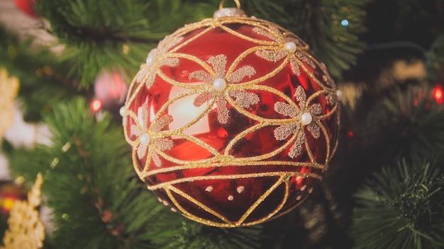 Close-upbeeld van rood met gouden snuisterij die op kerstboom hangt