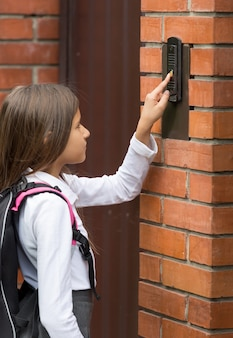 Close-upbeeld van schattig schoolmeisje dat aan de deurbel rinkelt