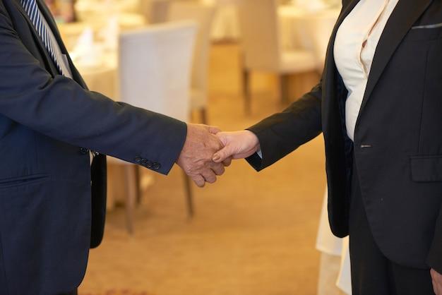 Close-upbeeld van senior zakenpartners die handen schudden voordat ze in restaurant vergaderen