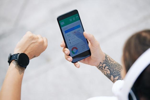 Close-upbeeld van sportvrouw gezondheidstoepassing op smartphone controleren bij het synchroniseren met smartwatch
