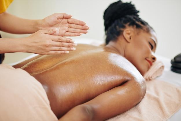 Close-upbeeld van therapeut die rug van mooie jonge zwarte vrouw met organische oliën masseert