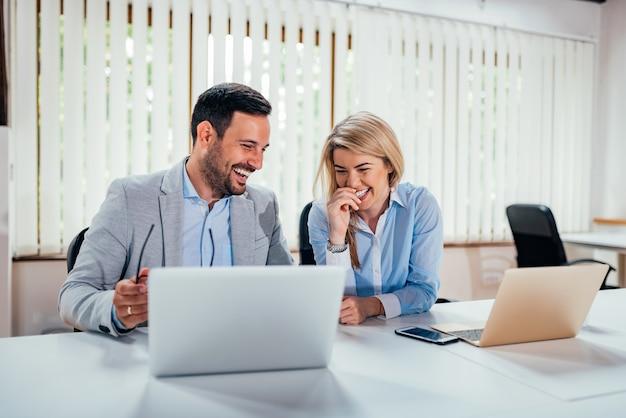 Close-upbeeld van twee bedrijfsmensen die in het coworking van bureau lachen.