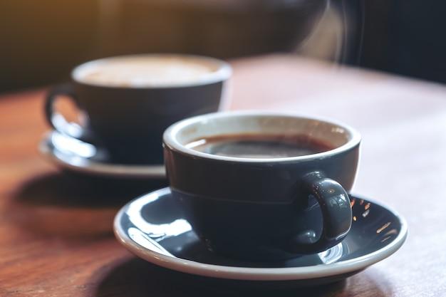 Close-upbeeld van twee blauwe koppen hete lattekoffie en americano-koffie op uitstekende houten lijst in koffie