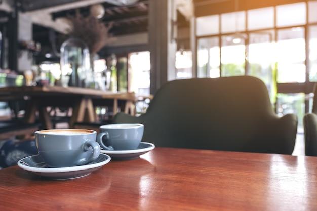 Close-upbeeld van twee blauwe koppen hete lattekoffie op uitstekende houten lijst in koffie
