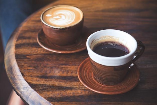 Close-upbeeld van twee koppen hete lattekoffie en zwarte koffie op uitstekende houten lijst in koffie
