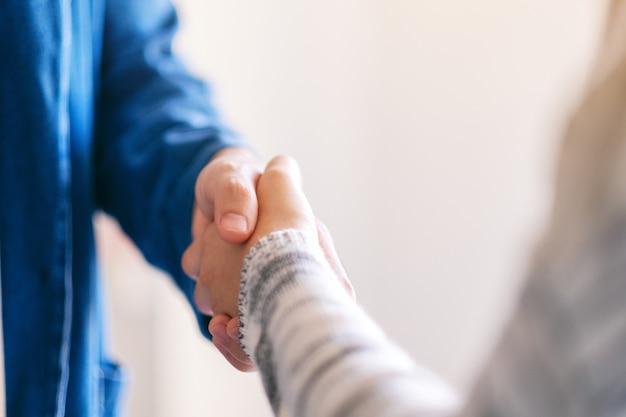 Close-upbeeld van twee mensen die elkaar de hand schudden