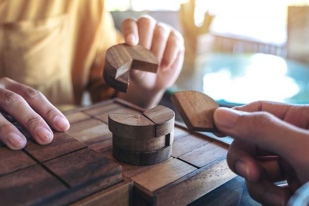 Close-upbeeld van twee mensen die en rond houten puzzelspel spelen bouwen